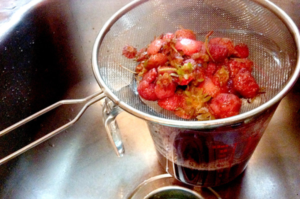 Squeezing every drop of taste and nutrients out of these hulled strawberry tops; boiled and strained.